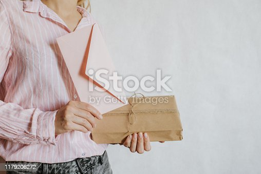 istock Woman holds in hand paper envelope and box. New mail, message. Postal service. Young girl want send or receive letter and package. Blank envelope, empty space. People communication. Envelope closeup 1179206272