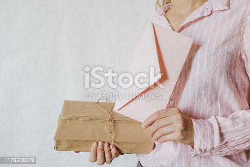 istock Woman holds in hand paper envelope and box. New mail, message. Postal service. Young girl want send or receive letter and package. Blank envelope, empty space. People communication. Envelope closeup 1179206276