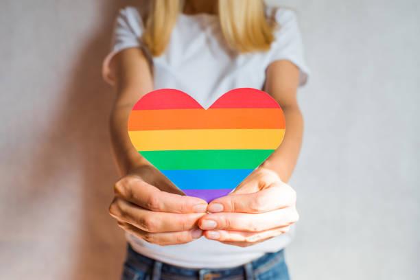 女は虹の色で心を手に握る。若い美しい少女lgbtの歴史月間。プライド・マンスレズビアンゲイバイセクシャルトランスジェンダー。lgbt フラグ。愛、人権、寛容。lgbtq+ - lgbtqi  ストックフォトと画像