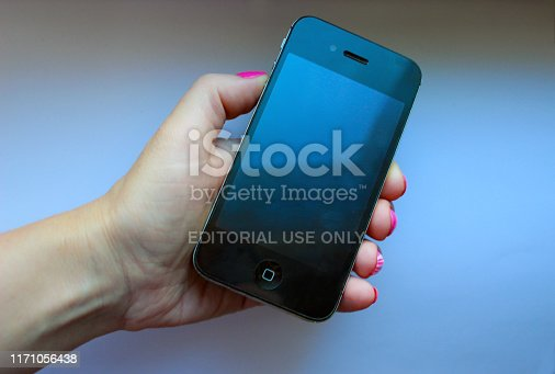 istock Woman holds in her hand a black Iphone 4S. Iphone 4S on a white background 1171056438