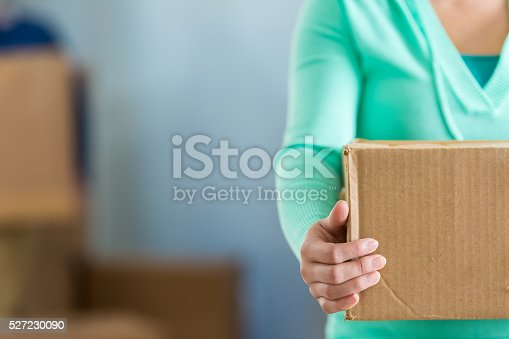 istock Woman holds moving box 527230090