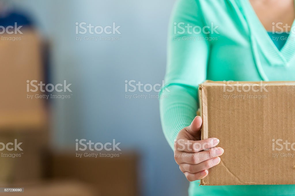 Woman holds moving box stock photo