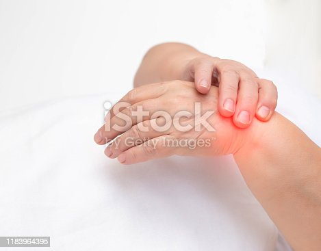 668285874istockphoto Woman holds on wrist joint on a white background. The concept of pain and inflammation of the wrist joint, tunnel syndrome and arthritis, copy space 1183964395