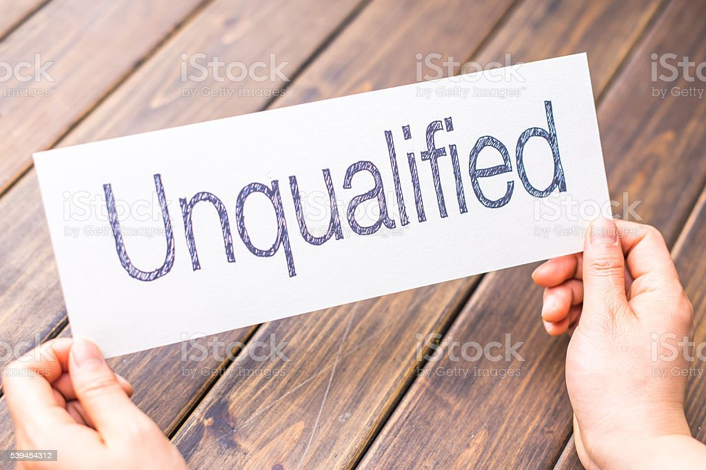 woman holds paper with word unqualified in office stock photo