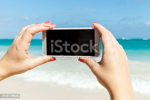 599114758istockphoto Woman holds phone for taking beach photo 519126630