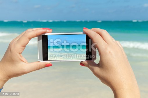 599114758istockphoto Woman holds phone in hands for taking photo 519126570