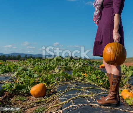 istock Woman Holds Pumpkin at Side 940204012