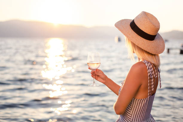 Woman holds wineglass at background of sunset sea or ocean. Blond girl is wearing in casual striped dress, straw hat. Beautiful woman is relaxing, traveling and enjoying life in summer vacation. stock photo