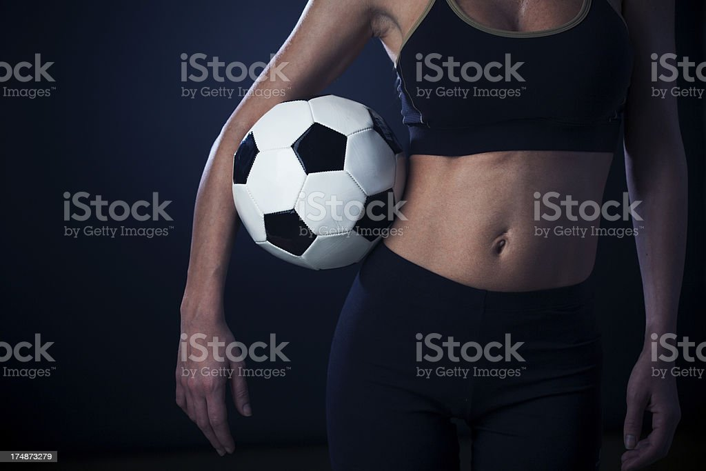 Woman holidng a soccer ball on hip. royalty-free stock photo