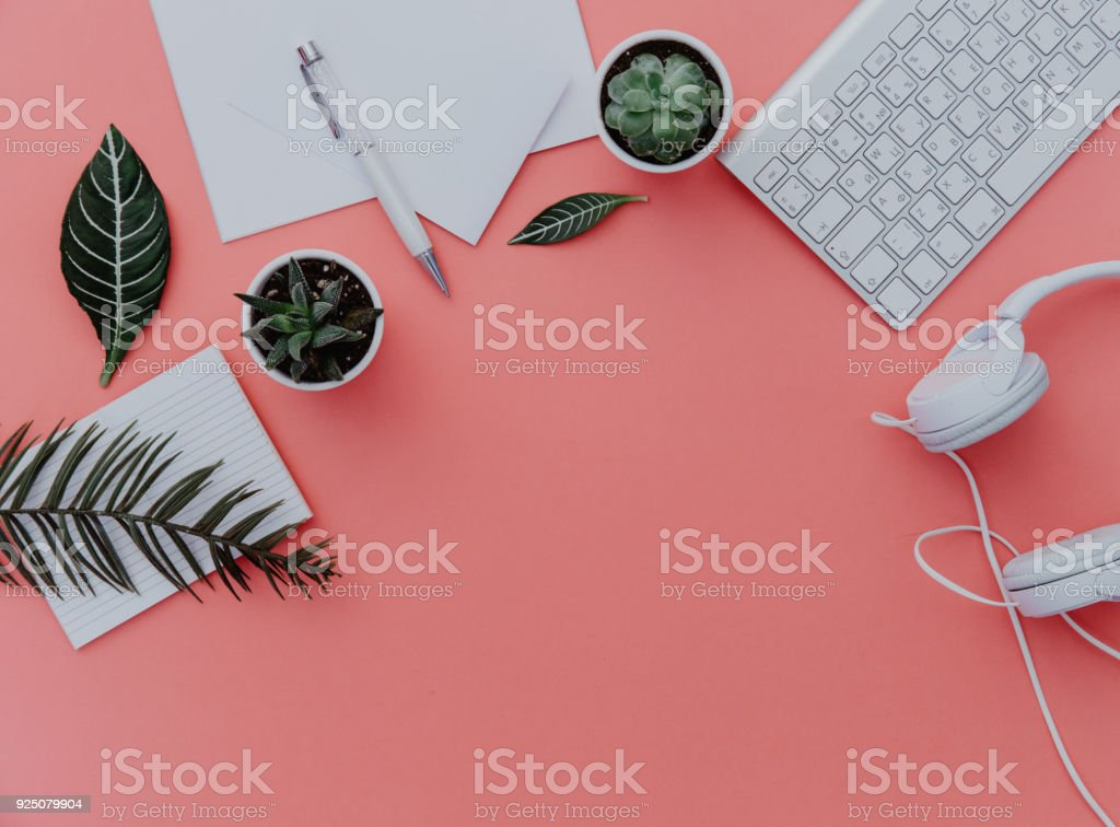Woman home office desk workspace with laptop, headphones and plants over pastel. Flat lay, top view. stylish female concept. stock photo