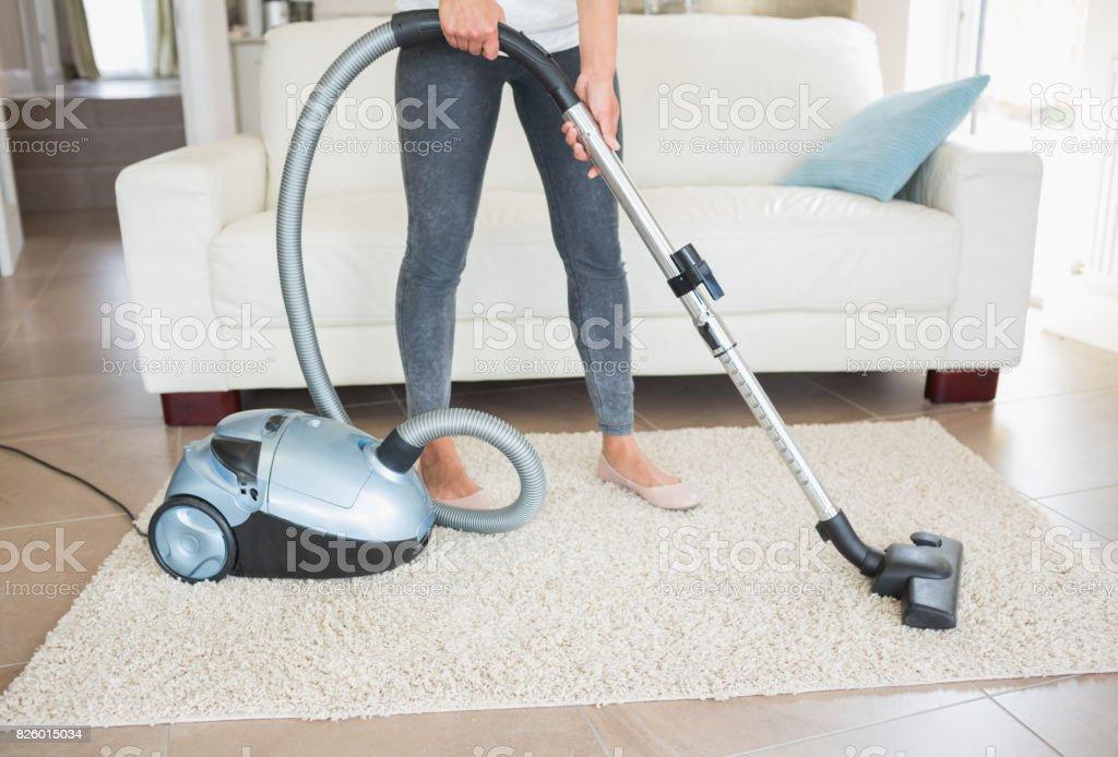 Woman hoovering rug - foto stock