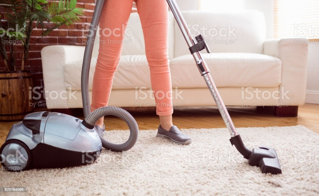 Woman hoovering the rug - foto stock