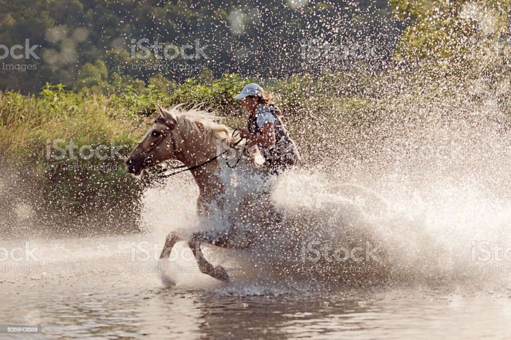 Woman horse rider running in the river stock photo