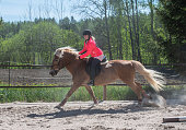 istock Woman horseback riding on ranch 1256467648