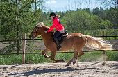 istock Woman horseback riding on ranch 1256467651