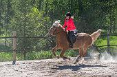 istock Woman horseback riding on ranch 1256467677