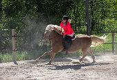 istock Woman horseback riding on ranch 1256467697