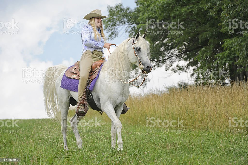 Woman Horseback Riding on White Arabian Horse, American Western Cowgirl stock photo