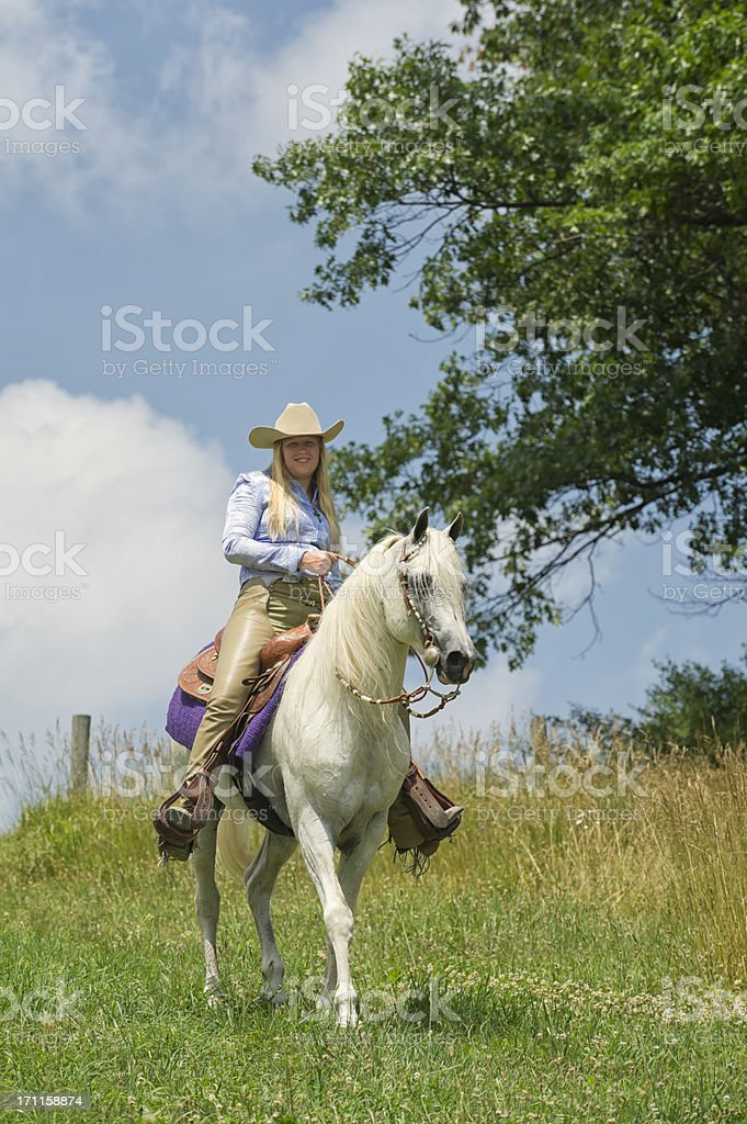 Woman Horseback Riding on White Horse, American Western Cowgirl stock photo