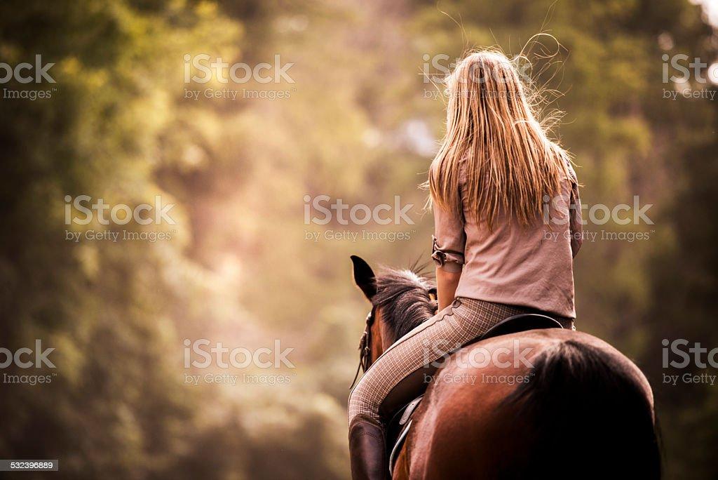 Woman horseback riding. stock photo