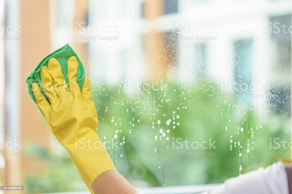 Woman housekeeper cleaning the mirror with green cloth. stock photo