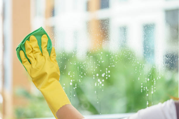 Woman housekeeper cleaning the mirror with green cloth. Woman housekeeper cleaning the mirror with green cloth. cleaning equipment stock pictures, royalty-free photos & images