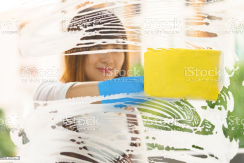Woman housekeeper cleaning the mirror with yellow sponge stock photo