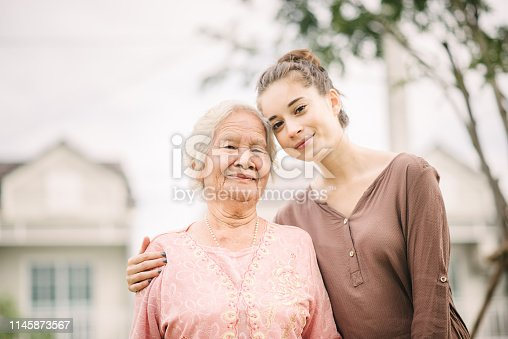 Happy young caucasian woman hugging elderly Asian woman outdoor