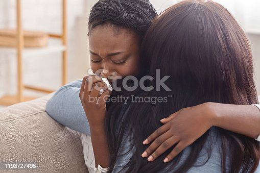 Condolence and support concept. Caring woman hugging her crying black girlfriend, comforting her after receiving bad news