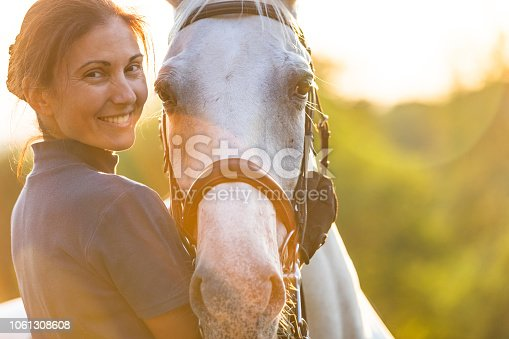 Woman hugging her horse, looking at camera