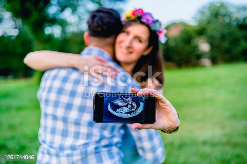 Young smiling woman hugging her husband while showing ultrasound image on her cellphone