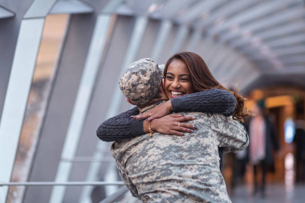 Woman hugging her partner after returning home from service A beautiful woman of Indian descent passionately hugs her partner as she greets him returning from his military service. He is wearing a military uniform. husband stock pictures, royalty-free photos & images