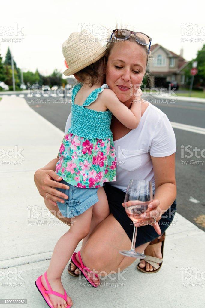 Woman hugging little girl on family gathering. stock photo