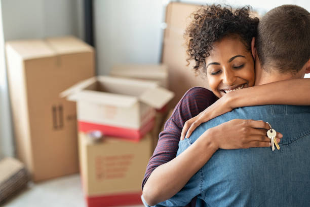 Woman hugging man and holding home keys Young african woman holding home keys while hugging boyfriend in their new apartment after buying real estate. Lovely girl holding keys from new home and embracing man. Happy couple in their apartment around cardboard boxes. house stock pictures, royalty-free photos & images