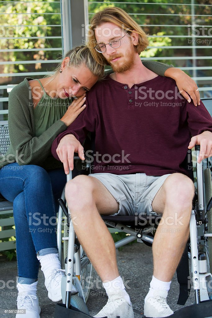 woman hugging man in wheelchair and looking sad stock photo