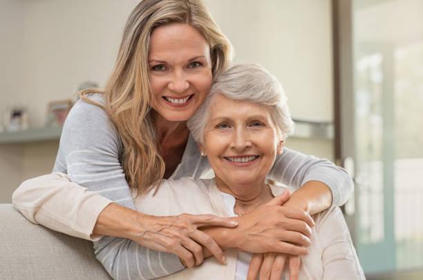madre abrazando mujer con amor - hija fotografías e imágenes de stock
