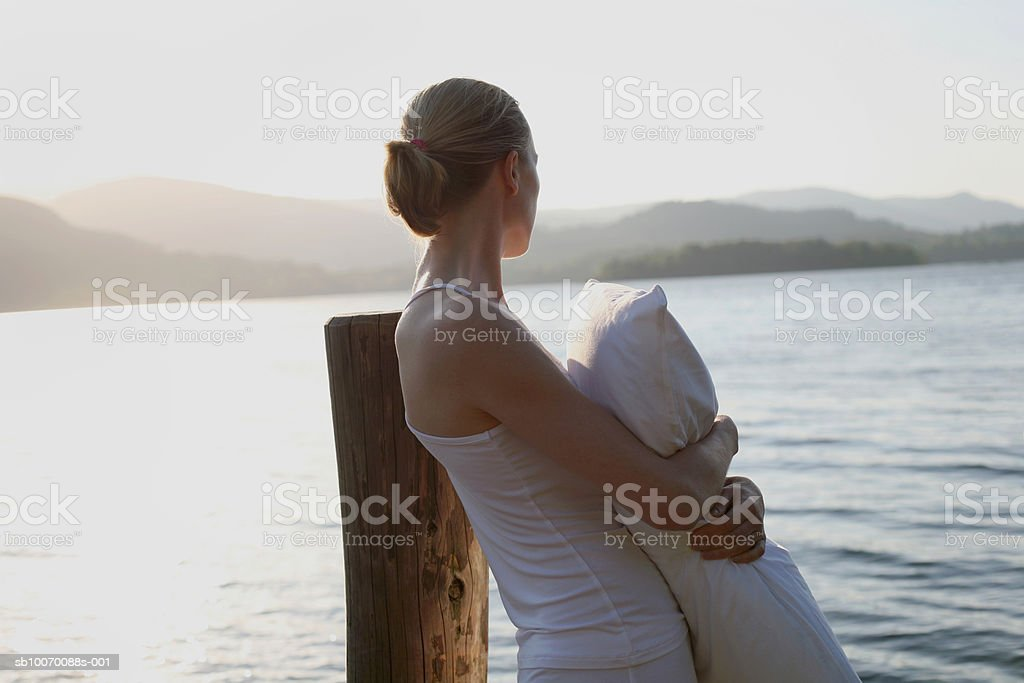 Woman hugging pillow and looking at lake Lizenzfreies stock-foto