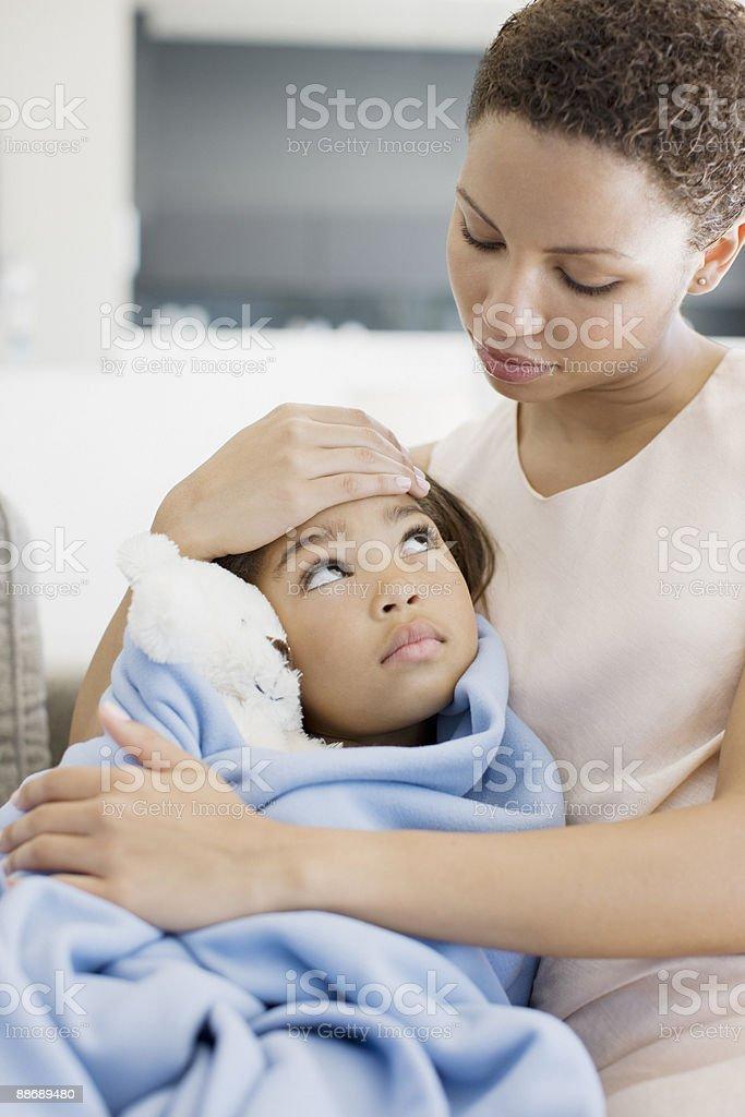 Woman hugging sick daughter stock photo