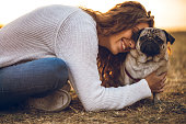 Young beautiful caucasian woman hugging with pug dog in a public park.