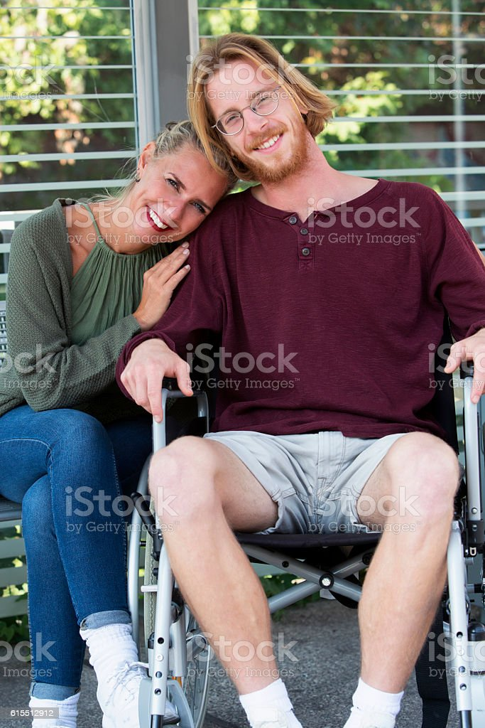 woman hugging young man in wheelchair stock photo