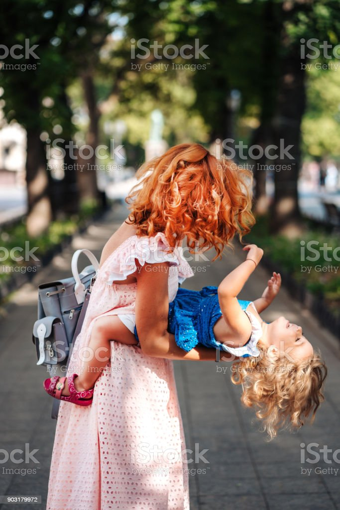 Woman hugs her daughter, holding her in her arms stock photo