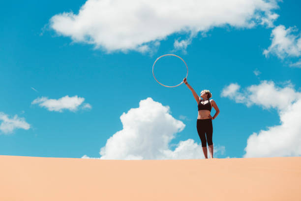 woman hula hooping with sky and clouds background - katiedobies stock pictures, royalty-free photos & images