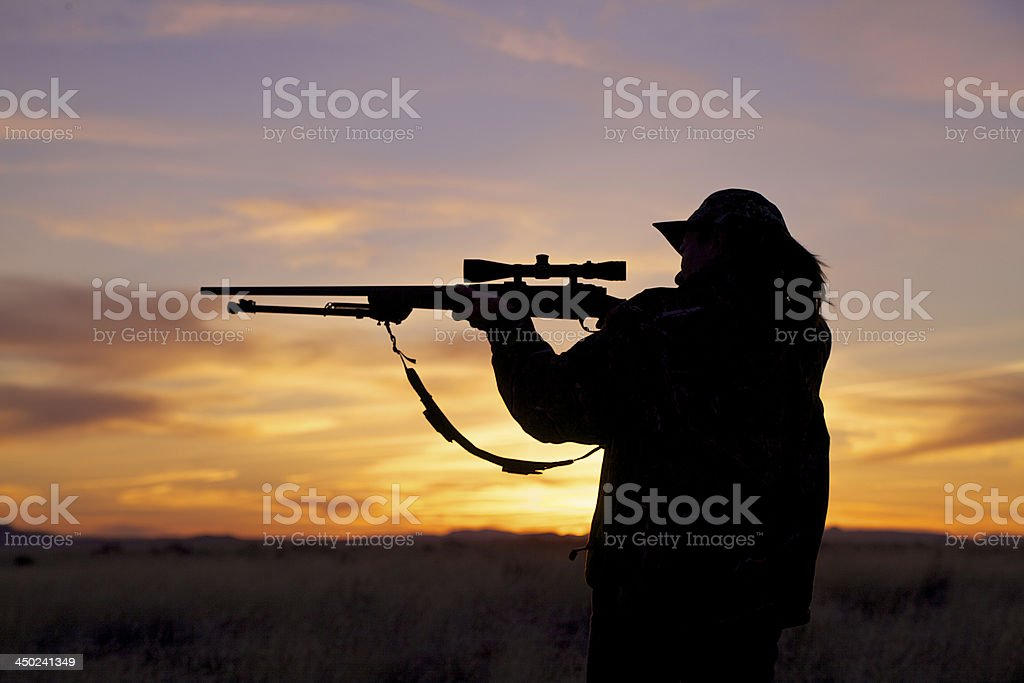 Woman Hunter Shooting at Sunset royalty-free stock photo