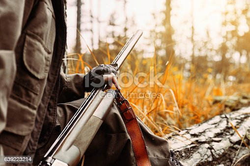 istock Woman hunter with a gun. Hunting in the woods. 639223214