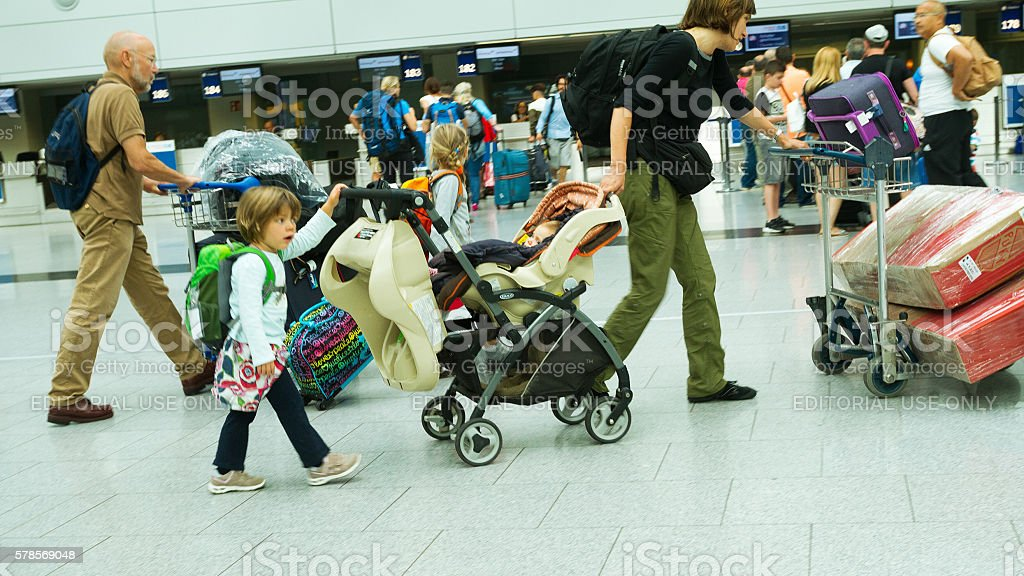 Woman hurry with luggage, baby buggy and kids stock photo