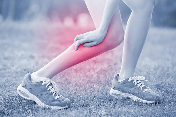 woman hurt leg in park - wadenkrämpfe was tun stock-fotos und bilder