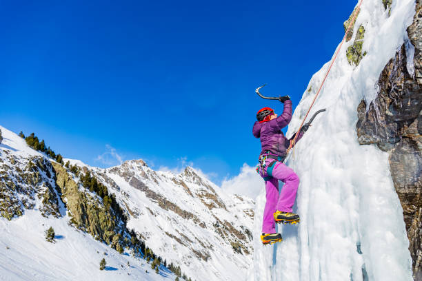 ピレネー山脈のフランスで凍った滝を登る女性氷 - アイスクライミング ストックフォトと画像
