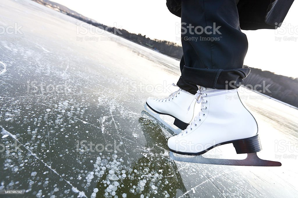 Woman ice skates with overview of a lake royalty-free stock photo