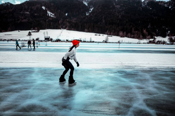 a woman ice skating on a frozen lake in winter - skate liberdade gorro imagens e fotografias de stock