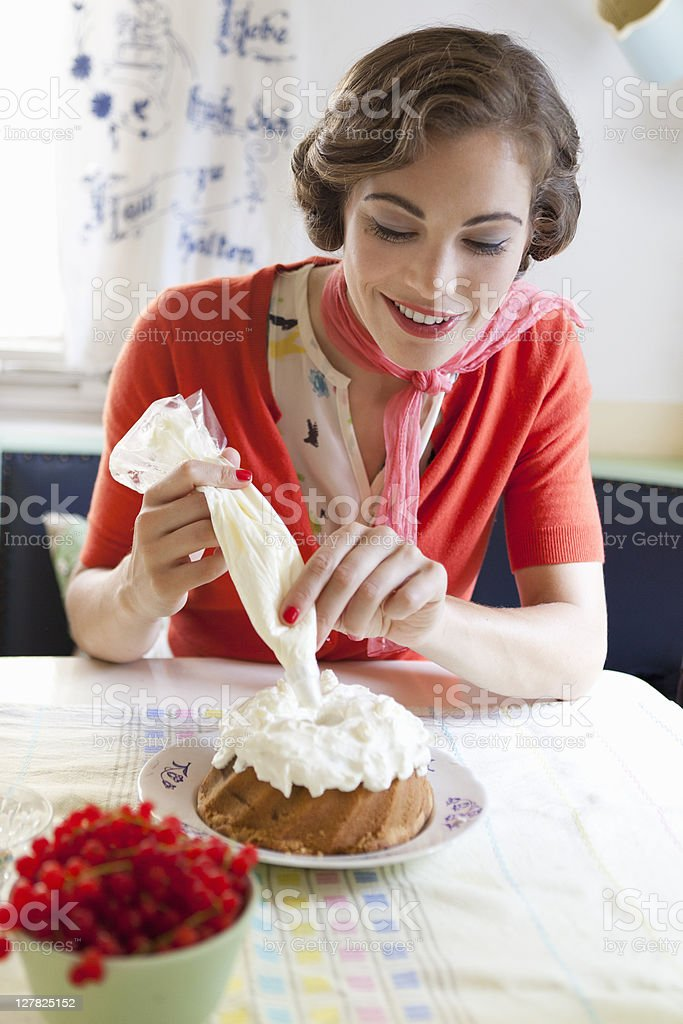 Woman icing a cake in kitchen stock photo